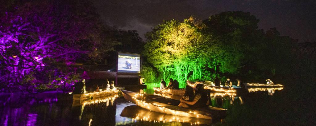 Barcos iluminados sobre lago, com pessoas vendo filme em telão