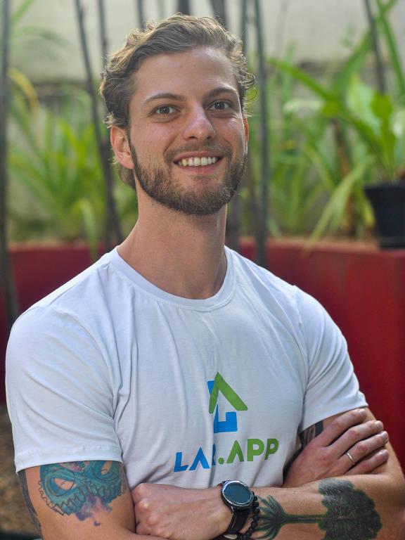 Rafael sorri para a câmera, veste camiseta e está de braços cruzados, que têm tatuagens