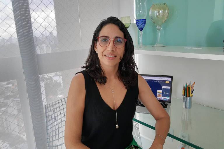 Ana Rita Oliveira, sentada em frente a uma mesa de vidro, que tem um notebook apoiado sobre ela