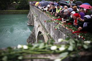 Bosnian Muslims toss 3000 roses in the River Drina after a mass funeral in Visegrad