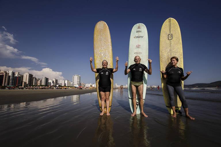 três pessoas idosas na beira do mar com trajes de surfista e as pranchas espetadas na areia - eles sorriem para a foto