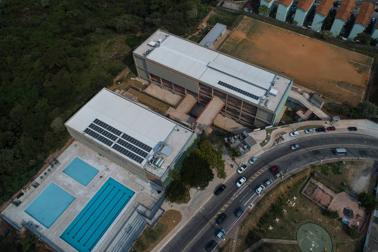 Vista aérea de complexo com dois prédios e três piscinas