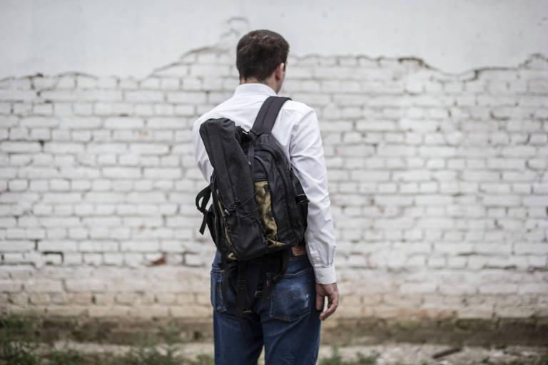 Um homem de calça jeans e camisa branca aparece de costas. Ele está à frente de uma parede branca de tijolos. Ele tem pele clara e cabelo escuro curto. Nas costas, sobre seu ombro direito, carrega uma mochila preta.
