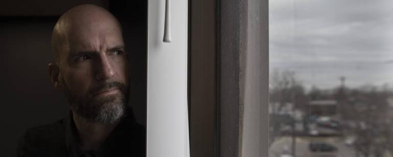 Nate Blake, careca e de barba, usando camiseta preta, olha pela janela, de onde se vê um estacionamento com carros