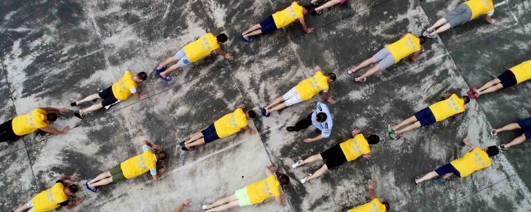 Homens com camisetas amarelas fazem flexões em um chão de cimento, vistos de cima