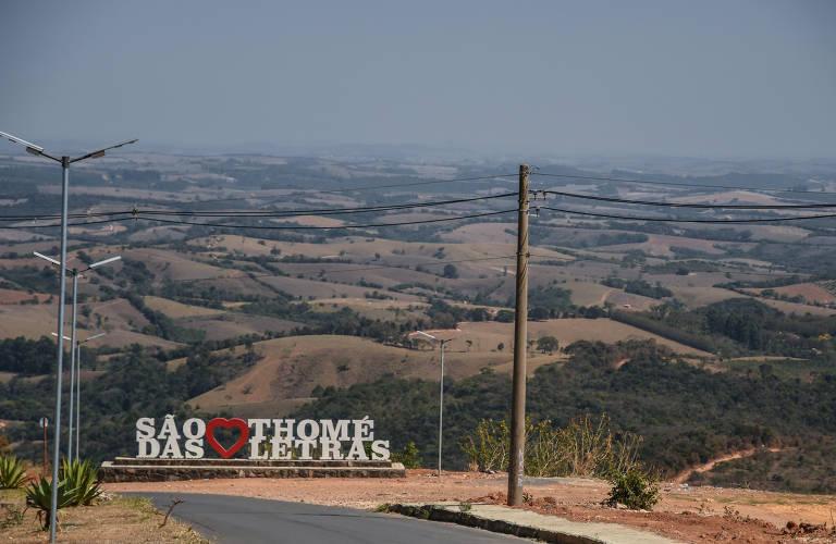 Letras brancas com o nome da cidade e ao fundo as montanhas de Minas Gerais.