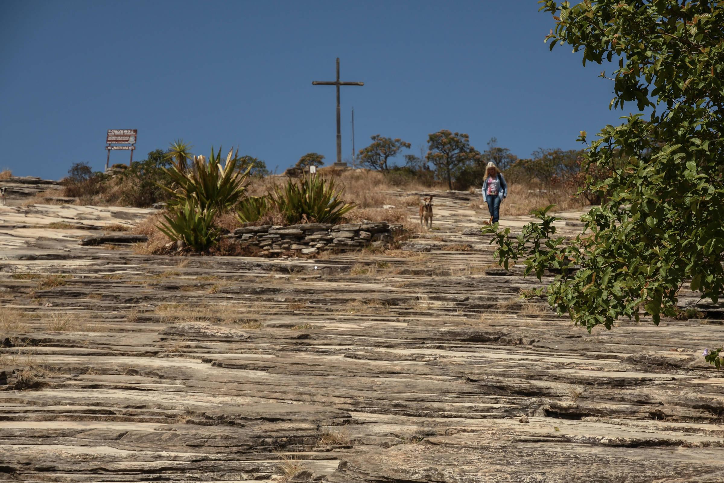 Mulher desce Morro do Cruzeiro, ponto turístico de São Tomé das Letras (MG), durante a pandemia