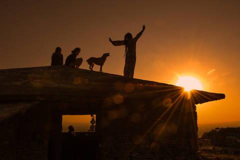 SÃO THOMÉ DAS LETRAS/ MINAS GERAIS/ BRASIL - 04/09/20 - :00h - RAIO X SOBRE A COVID NAS REGIÃO SUDESTE E NORDESTE DO BRASIL. Moradores celebram o pôr-do-sol na Casa da Pirâmide, ponto turístico que atraía centenas de visitantes antes da pandemia. ( Foto: Karime Xavier / Folhapress) . ***EXCLUSIVO***Especial - O Brasil das várias pandemias  #PraCegoVer Silhuetas de moradores celebram o pôr-do-sol .