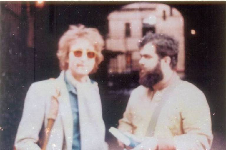 Homem com óculos ao lado de homem barbudo o olhando