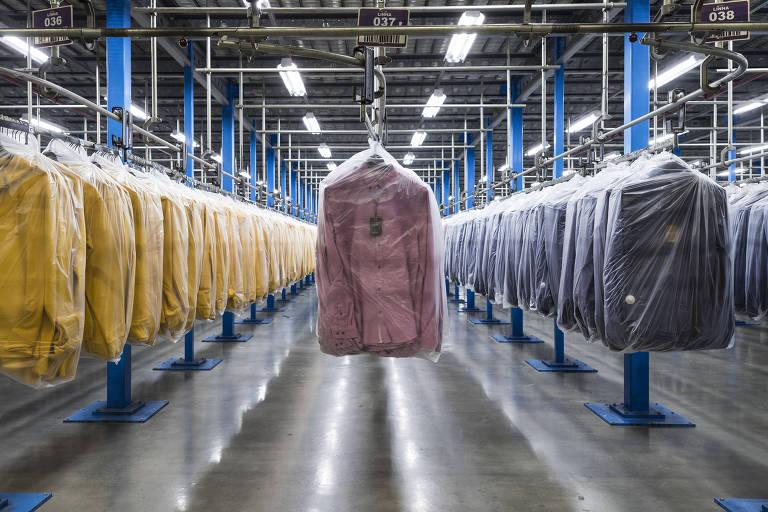 Vista frontal de peças de vestuários penduradas em três fileiras com casacos divididos nas cores amarela, rosa e azul escuro.
