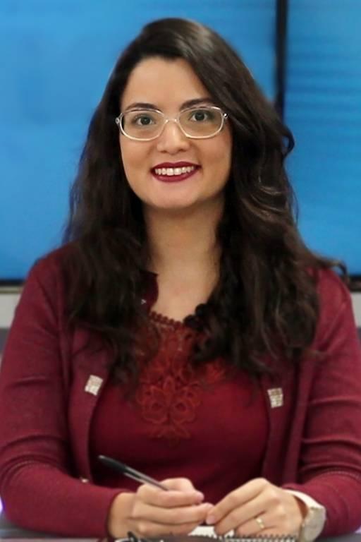 Mulher de cabelos castanhos, óculos, blusa e casaco vinho sorri