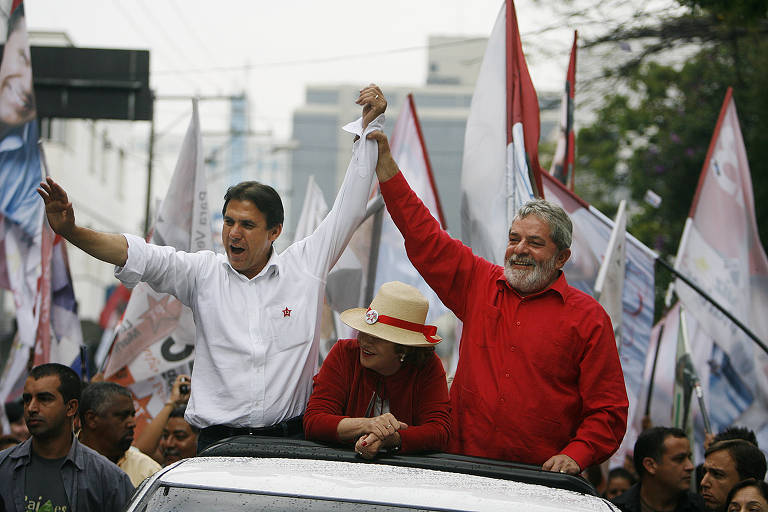 Marinho de camisa branca segurando no alto a mão de Lula, de camisa vermelha, na traseira de uma carro. No meio deles, abaixada, a primeira dama Marisa Letícia, de vermelho e chapéu. Atrás deles, várias bandeiras