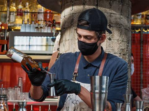 Bartender usa máscara e luvas para preparar drinque no bar Regô, na região central