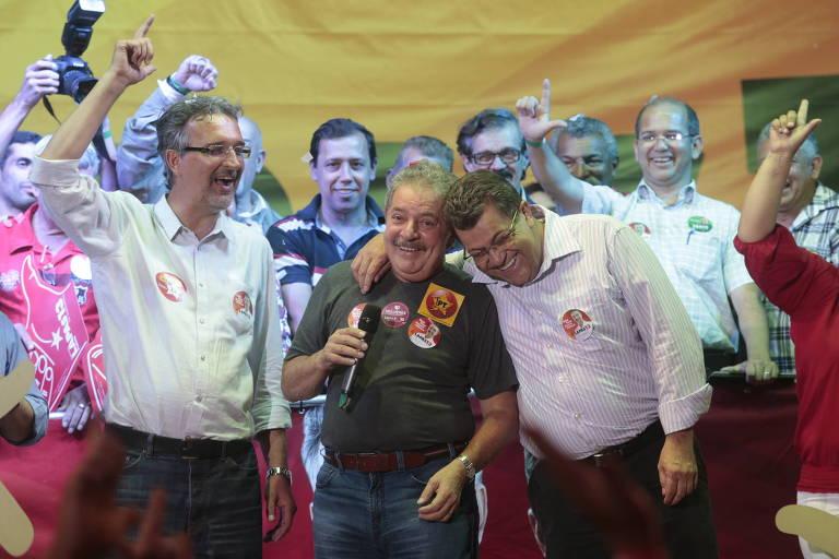Emídio inclinado sobre o ombro de Lula. Lapas e outros presentes fazem a letra L com a mão