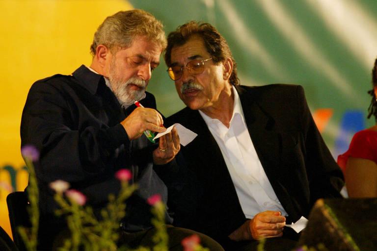 Lula escreve num papel ao lado de Pietá, que inclina o rosto para ler o bilhete