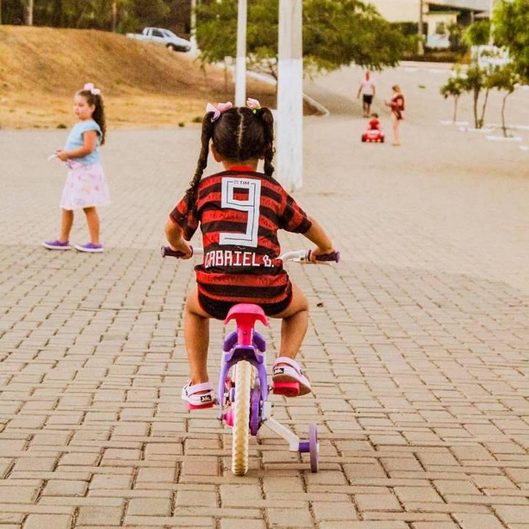 Criança, de costas, andando de bicicleta