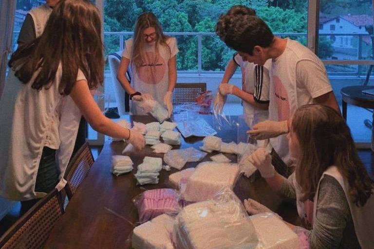 Jovens usam avental e estão em volta de pilhas de pacotes de absorventes.