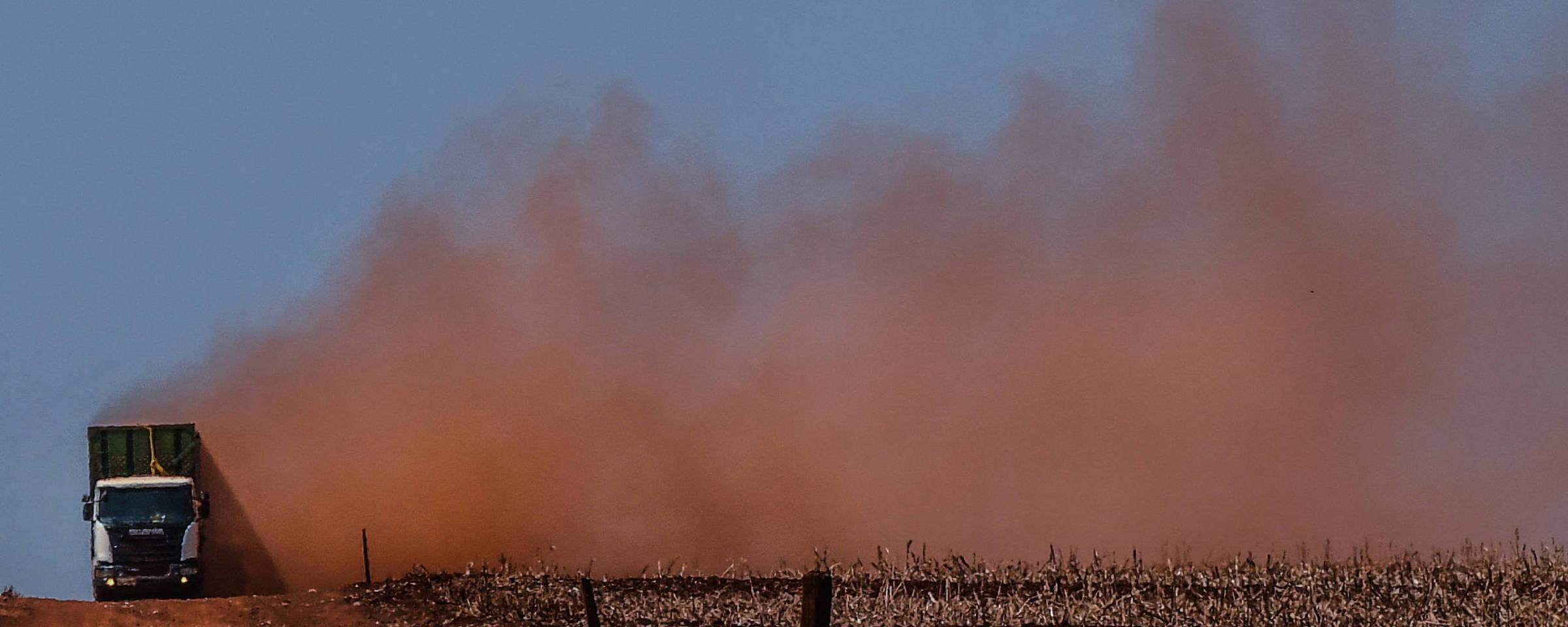 Caminhão em estrada de terra levanta poeira vermelha pelos campos