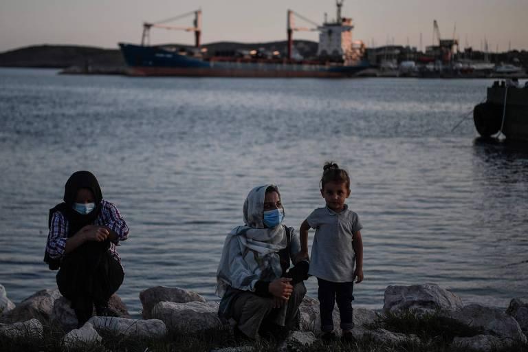 Imigrantes esperam para embarcar em ônibus que o levarão a campos para refugiados na Grécia
