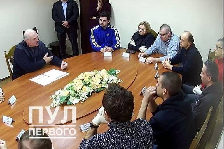 mesa de madeira oval com várias pessoas sentadas em reunião
