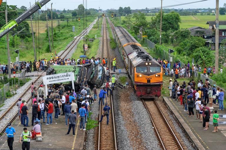 Multidão observa destroços de ônibus enquanto um trem passa na via férrea ao lado