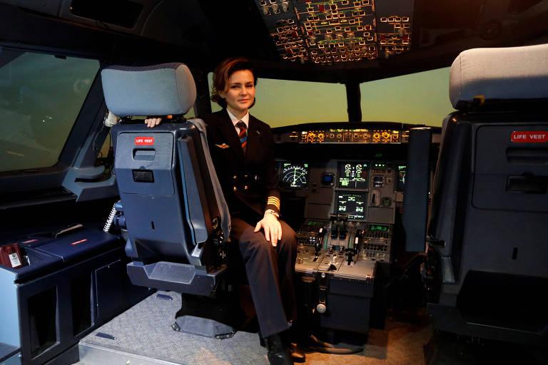 Mulher de cabelos castanhos curtos e uniforme de comandante de avião (terno azul marinho, gravata, luva branca) em cabine de piloto de avião