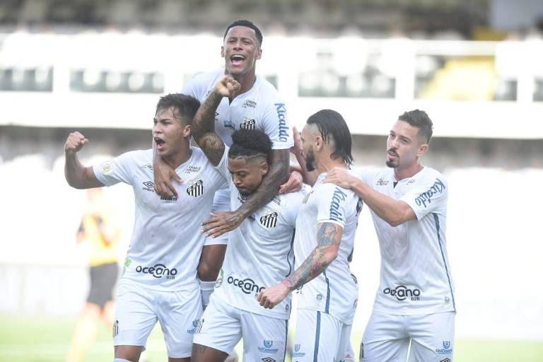 Marinho é abraçado pelos companheiros de Santos após marcar um gol contra o Grêmio