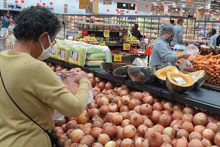 Mulher escolhe alimentos em supermercado.