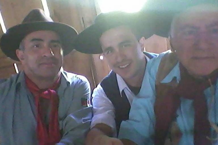 Os três homens sorriem para a câmera, vestidos com trajes típicos de gaúcho, com lenços no pescoço e chapéu