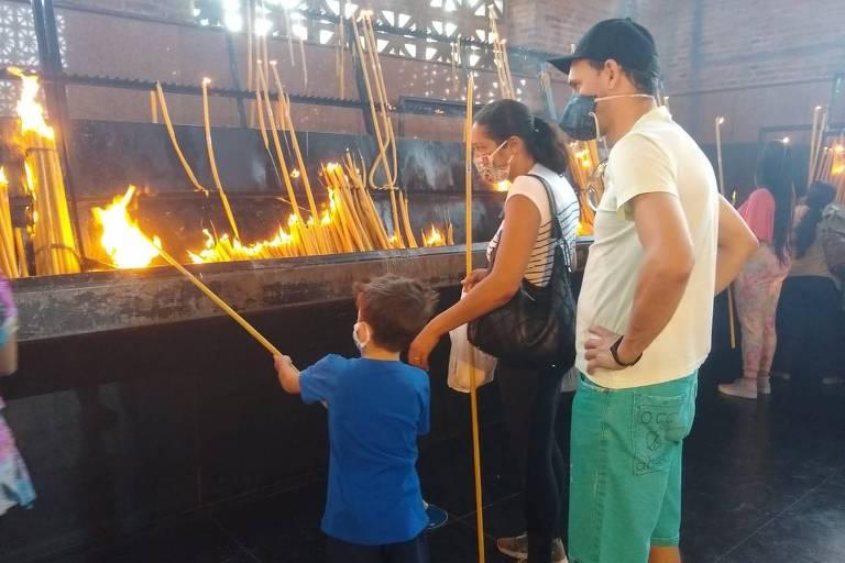 Auxiliado pela mãe, garoto segura grande vela, que é acesa no santuário