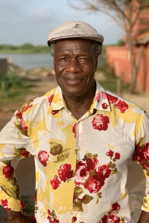 Homem negro vestido com boina e camisa florida