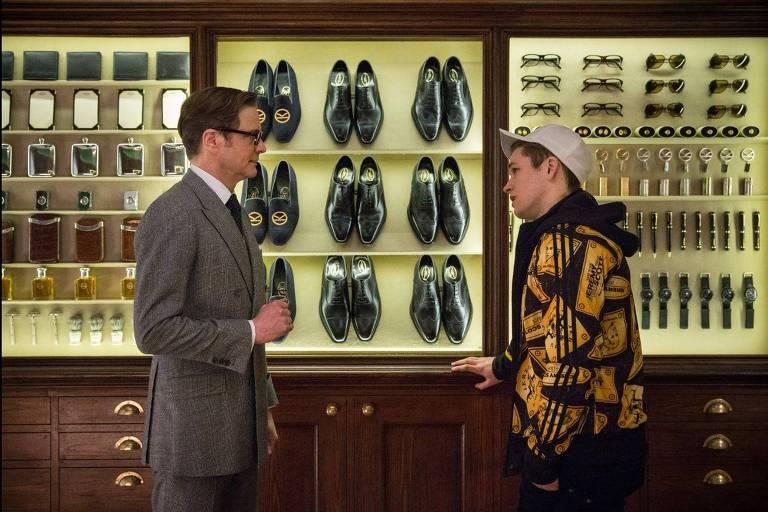 Homens conversam em frente a vitral com sapatos
