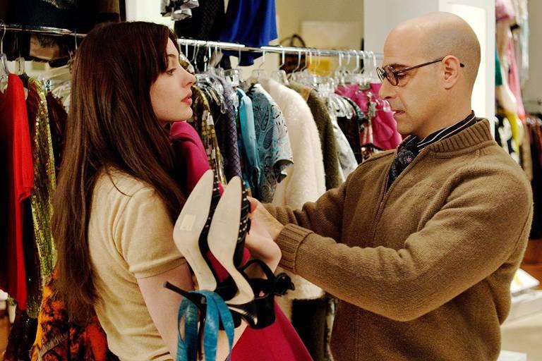Mulher e homem conversam ao lado de cabide repleto de roupas
