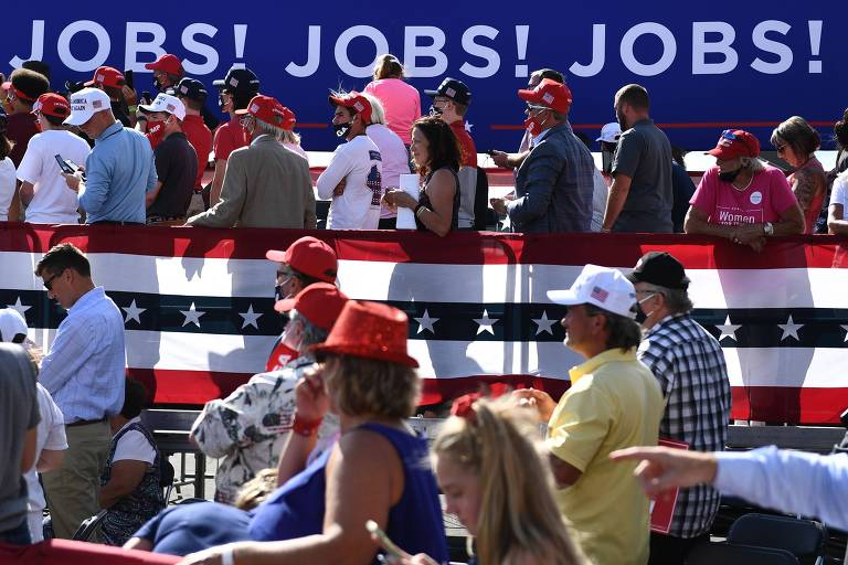 Apoiadores de Donald Trump em frente a cartaz que promete mais empregos nos EUA