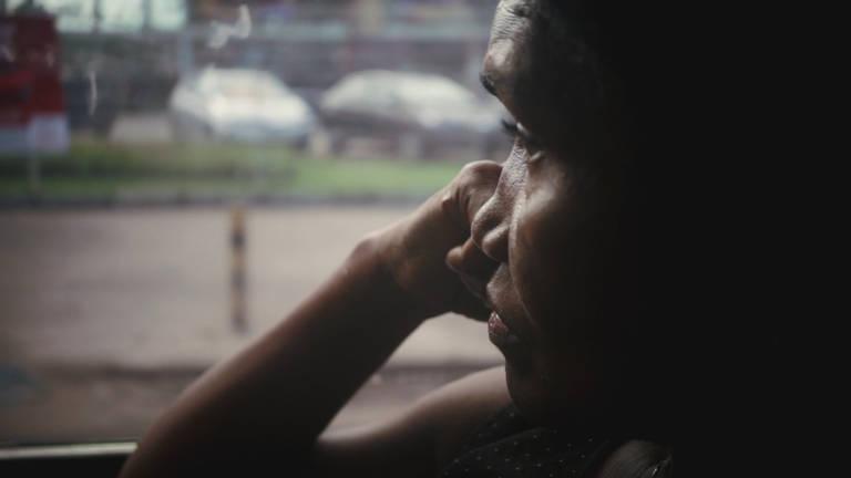 Maria Domingas, mulher negra na faixa dos 60 anos, olha pela janela do ônibus