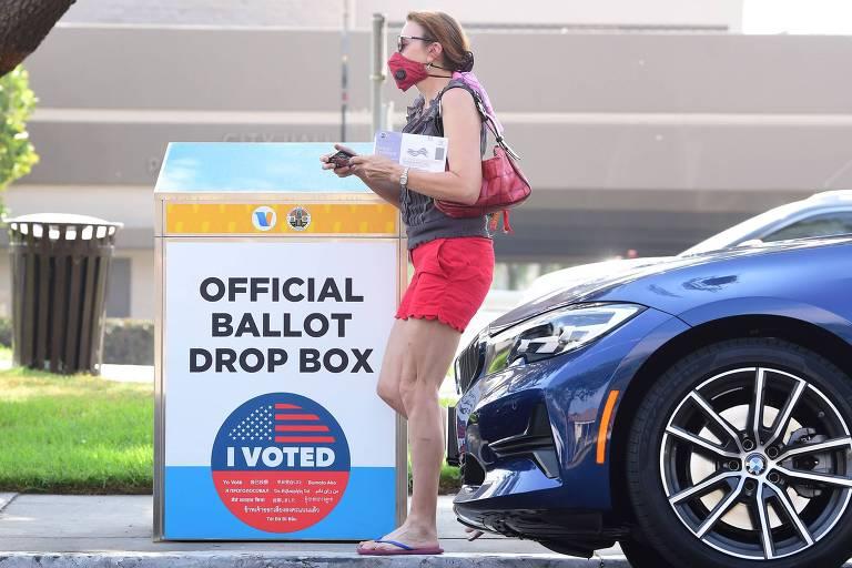 Mulher com cédula de voto por correspondência deposita envelope em urna para envio