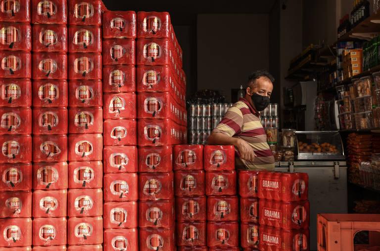 Homem de máscara  posa para foto atrás de vários engradados de bebidas dentro de um bar