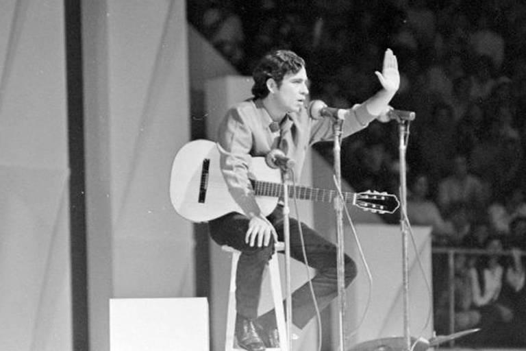 Sentado com o violão no colo, homem diante de microfone mostra a palma da mão esquerda para a plateia