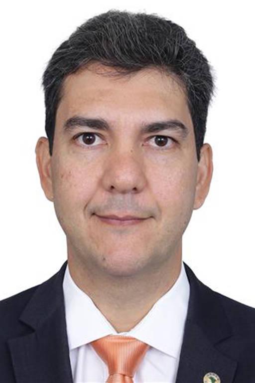 Retrato de homem de terno cinza e gravata rosa, com camisa branca.