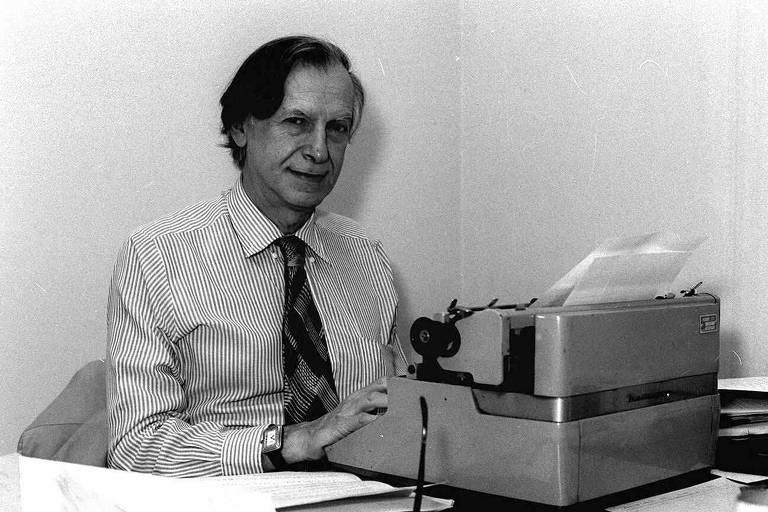 homem de camisa social e gravata, cabelos lisos penteados para o lado, sentado na frente de máquina de escrever