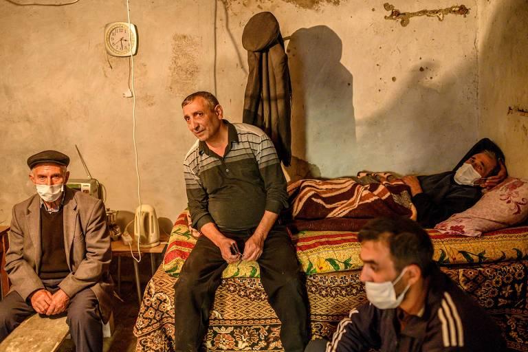Homens usam porão como abrigo contra bombardeios em Terter, no Azerbaijão