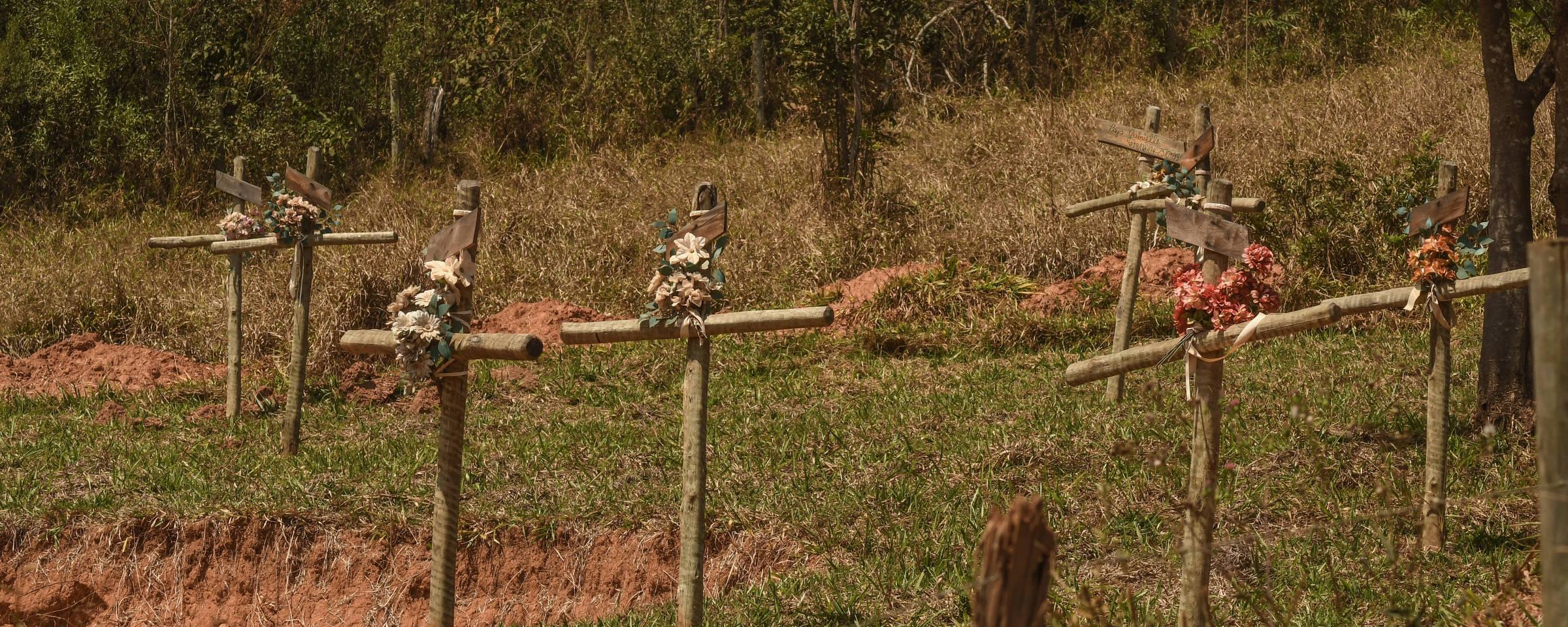 Cruzes de madeira com flores em terreno próximo ao local onde estava localizada a pousada.