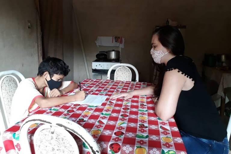 Uma mulher usando máscaras está diante de um adolescente, também de máscara, ambos apoiados em uma mesa de cozinha. Ele escreve em um caderno