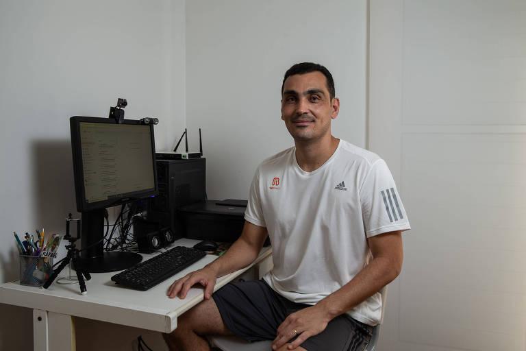 Professor está sentado em frente ao computador onde dá aula