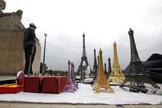 Souvenir vendor sells Eiffel tower models for tourists in front the Eiffel tower at the Trocadero in Paris
