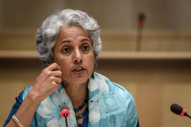 Mulher de meia idade, cabelos grisalhos, blusa azul turqueza, fala ao microfone