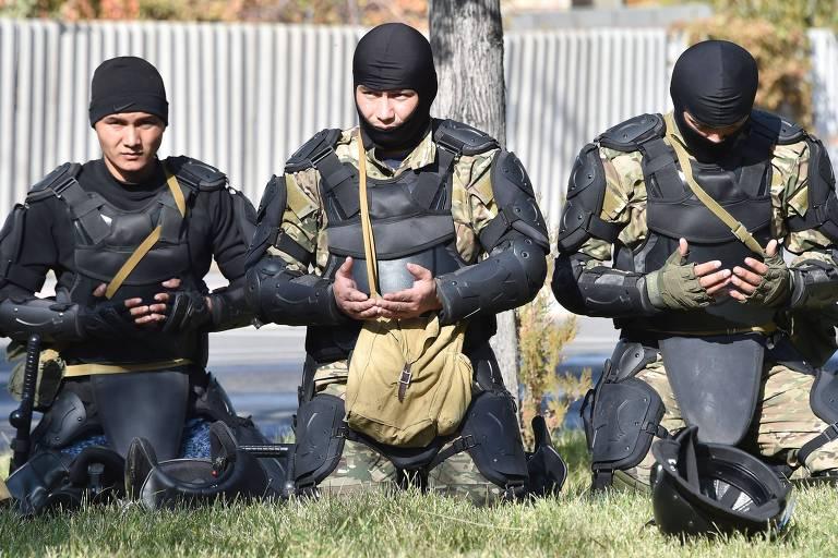 Membros muçulmanos da polícia de choque em Bishkek rezam ao lado da residência presidencial