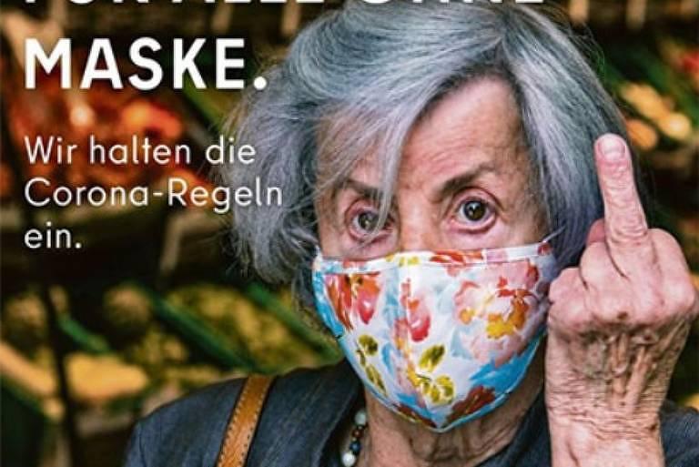 Anúncio mostra idosa de máscara florida mostrando o dedo do meio