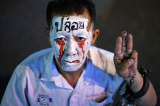 A man shows the three-finger salute during a gathering of pro-democracy protesters who demand the government to resign and to release detained leaders in Bangkok