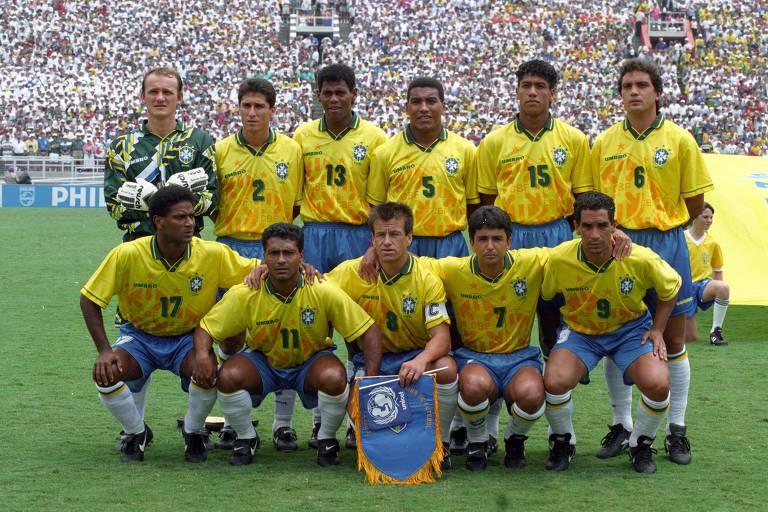11 jogadores vestindo camisa amarela da seleção enfileirados no campo posando para foto